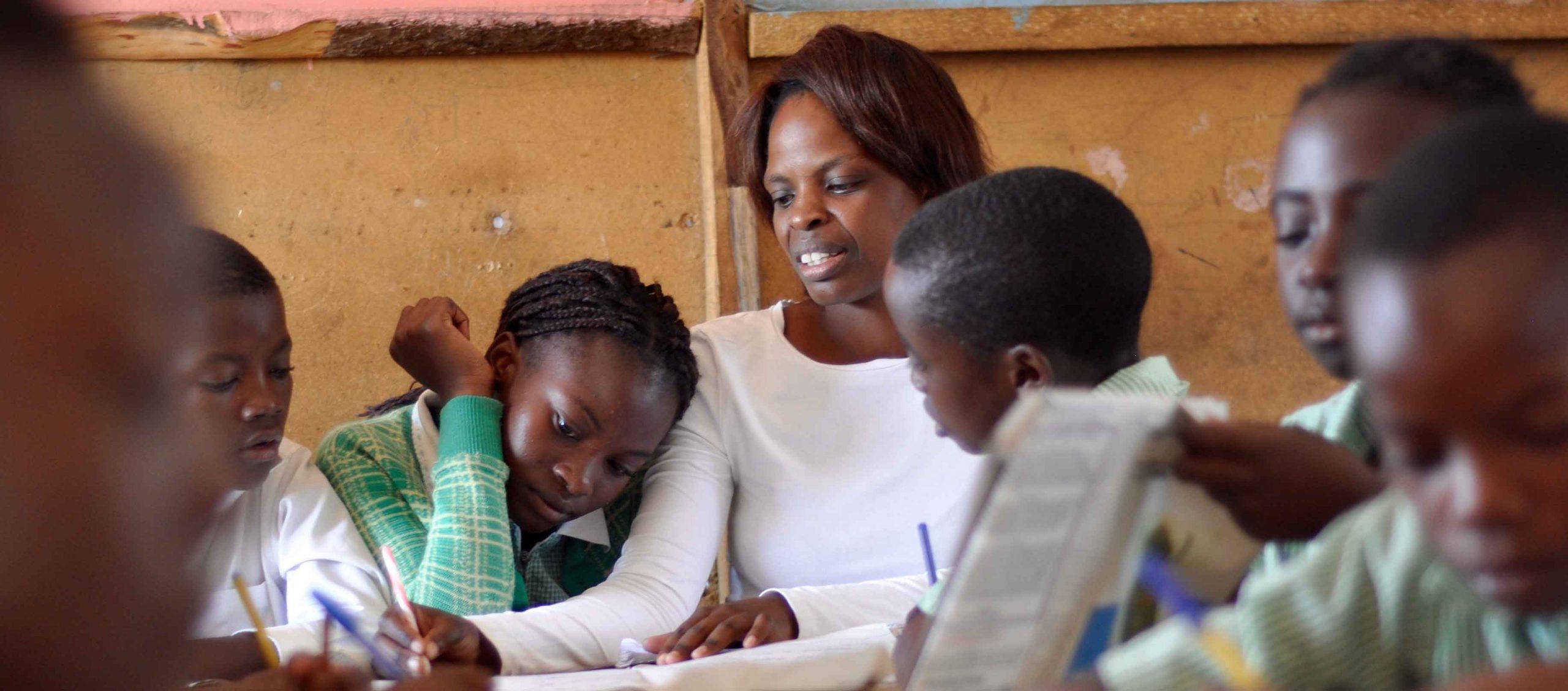 Women teaching children in classroom